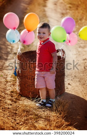 Portrait boy with colorful balloons on yellow field