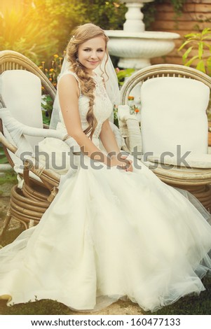 portrait bride in a wedding dress sits at chair