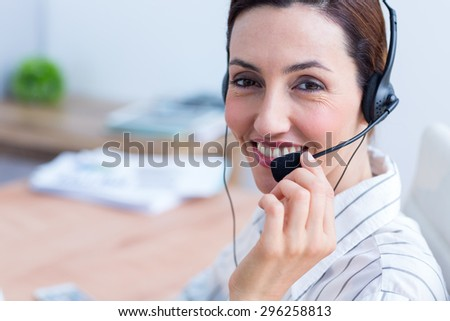 Portrait brunette businesswoman using headphone at the office