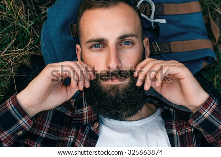 Portrait brutal bearded hipster man in the forest - stock photo