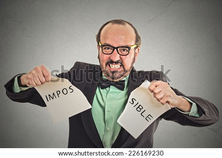 portrait business man tearing word impossible written on paper isolated on grey wall office background. Human face expression emotion determination attitude  - stock photo