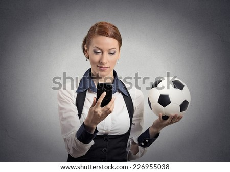 Portrait business woman looking on cell smart phone watching game holding football isolated grey wall background. Positive emotion, face expression. Data plan online gaming. Team leadership concept  - stock photo