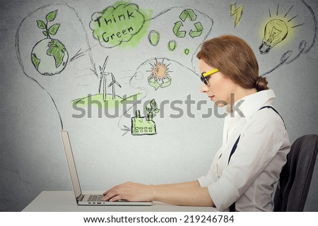Portrait business woman working on computer solving ecology, renewable energy, global warming problems, isolated grey wall background. Green planet, sustainable energy, recycling, wind power concept - stock photo