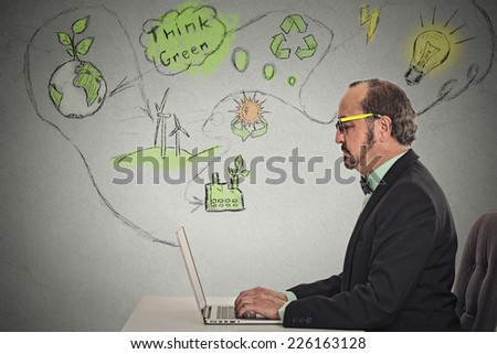 Portrait businessman working on computer solving ecology renewable energy, global warming problems isolated grey wall office background. Green planet, sustainable energy, recycling, wind power concept - stock photo