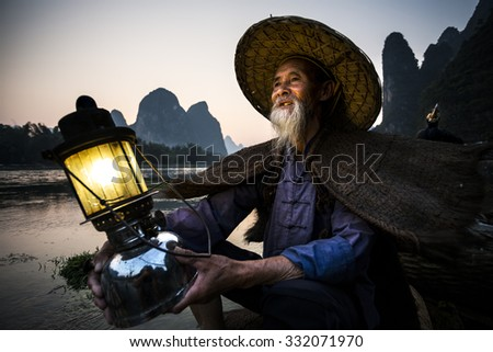 portrait by gas lamp of a traditional cormorant fisherman on Li river near Xingping, Guangxi province, China. - stock photo