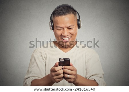 Portrait casual smiling young man listening music on cell phone isolated on grey wall background. Positive facial expression emotion. Technology leisure concept  - stock photo