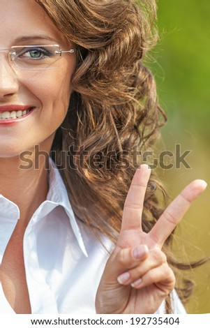 portrait charming young gay woman glasses shows sign victory background road park - stock photo