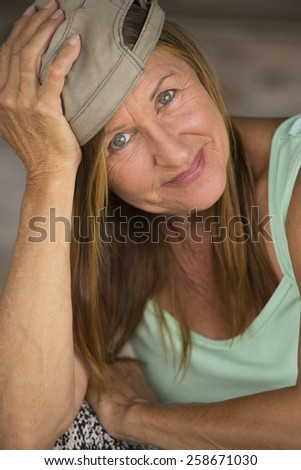 Portrait cheeky attractive active mature woman wearing green sporty top and cap, happy fit confident relaxed expression, blurred background.