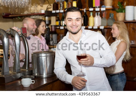Portrait cheerful man waiting for table in restaurant and drinking wine at tavern
