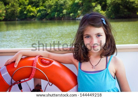 Portrait child ,happy girl on boat with red life-belt - stock photo