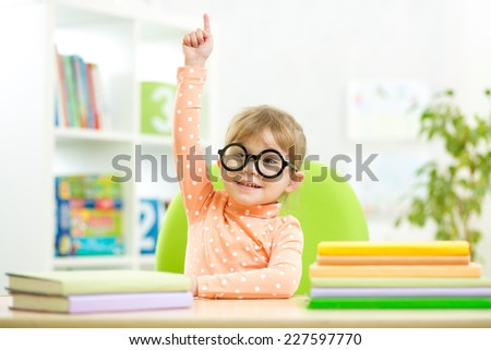Portrait clever kid child girl with books indoors