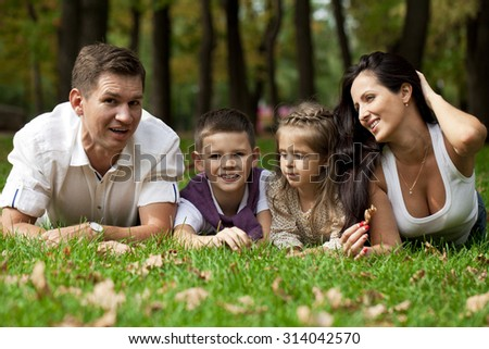 Portrait close up of happy family lying down in the garden on background of autumn park