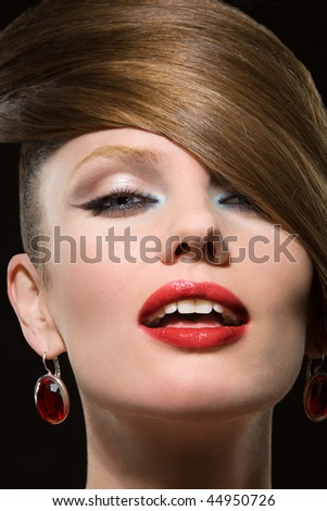 Portrait close-up of the young beautiful woman in earrings with jewels on black background. - stock photo