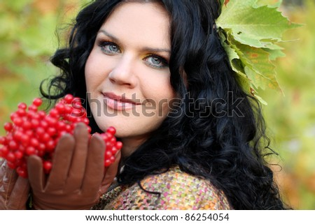 Portrait close up of woman with red berries, over green nature - stock photo