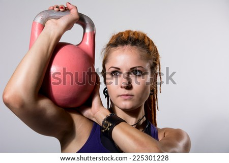 Portrait close up of young attractive female doing kettle bell exercise on grey background. Fitness woman working out. Crossfit exercise. - stock photo
