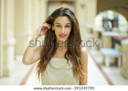 Portrait close up of young beautiful brunette woman in beige dress in the shop - stock photo
