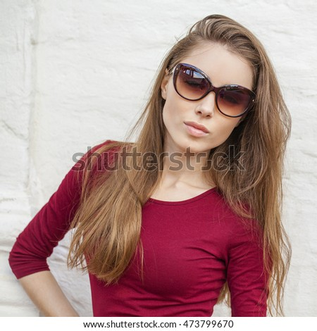 Portrait close up of young beautiful brunette woman in white fashion sunglasses, summer street outdoors