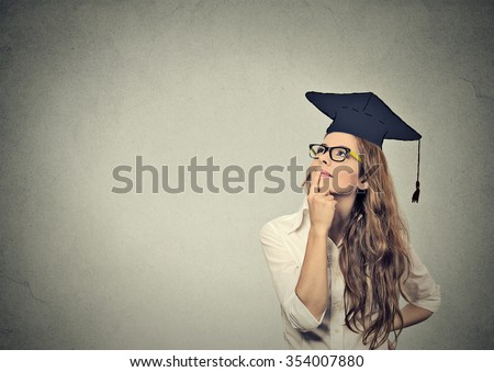 Portrait closeup beautiful thoughtful graduate graduated student girl young woman in cap gown looking up thinking isolated gray wall background. Graduation ceremony future career concept - stock photo
