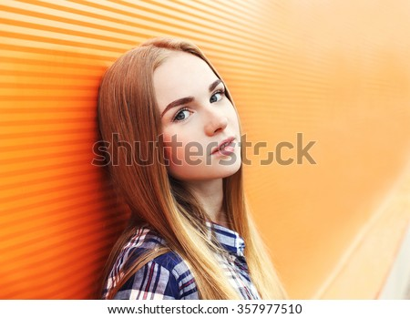 Portrait closeup beautiful young girl over colorful background - stock photo