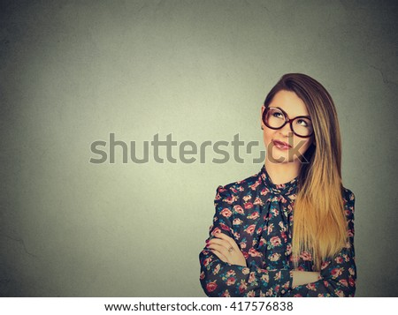Portrait closeup funny confused young skeptical woman in glasses thinking looking up isolated on gray wall background copy space above head. Human expressions, emotions, feelings, body language - stock photo
