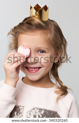 Portrait closeup of a young little girl with blonde hair and small gold crown on her head, eating a sweet macaroon. - stock photo