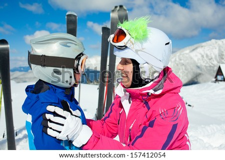 Portrait closeup of happy smiling boy in ski goggles and a helmet with his mother - stock photo
