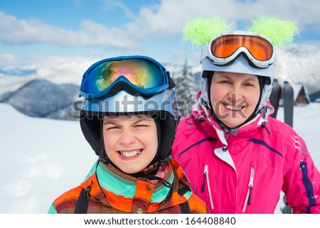 Portrait closeup of happy smiling girl in ski goggles and a helmet with his mother
