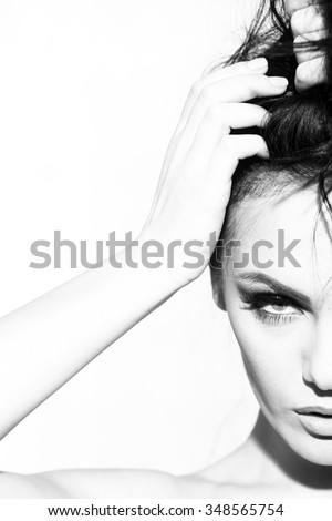 Portrait closeup of one pretty young sensual elegant sexy woman holding long curly hair with hand has bright makeup standing indoor looking forward black and white, vertical picture