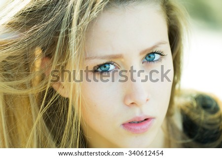 Portrait closeup of pretty blond girl with long straight hair blue eyes and parted lips looking at camera posing outside on light blurred background, horizontal picture