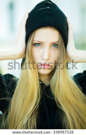 Portrait closeup of pretty blond girl with straight long hair flowed over her breast wearing black hood pin hands to head posing on streetscape background, vertical picture