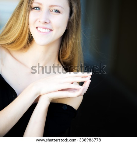 Portrait closeup of smiling pretty blond girl with long hair big joyful smile locking finger pads posing in black bare shoulders outside on blurred background, square picture - stock photo