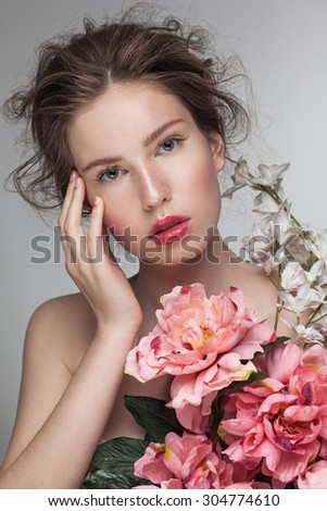 Portrait closeup of young sensual woman looking at camera. Perfect nude fresh makeup, clean clear skin and daily hairstyle with flowers, pink lip gloss and moon manicure. Pink flowers peony.
