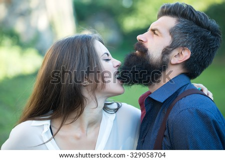 Portrait closeup view of beautiful funny young pair of woman biting man with long lush black beard standing sunny day outdoor on green grass on natural backdrop, horizontal photo - stock photo