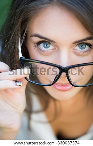 Portrait closeup view of one beautiful business young stylish woman in office black glasses looking forward outdoor on natural background, vertical photo - stock photo