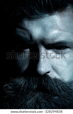 Portrait closeup view of one halloween holiday celebration character senior man with spooky painted face of zombi and long lush beard looking forward black and white, vertical picture