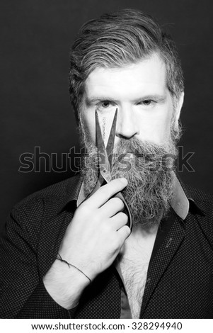 Portrait closeup view of one halloween holiday celebration character senior man with spooky painted face of zombi and long white lush beard holding scissors black and white, vertical picture