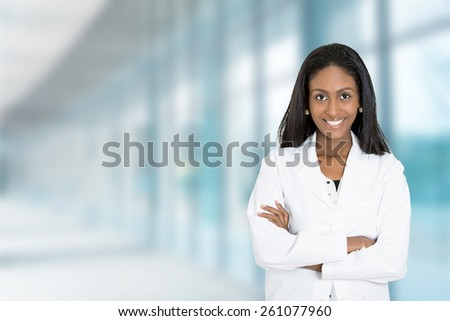 Portrait confident African American female doctor medical professional standing isolated on hospital clinic  hallway windows background. Positive face expression  - stock photo
