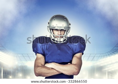 Portrait confident of American football player with arms crossed against rugby stadium
