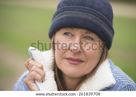 Portrait confident serious attractive mature woman outdoor, wearing warm bonnet and wool jacket, blurred green background, copy space. - stock photo
