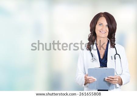 Portrait confident smiling mature female doctor medical professional standing isolated on hospital clinic hallway windows background. Positive face expression  - stock photo