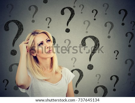 Portrait confused thinking woman bewildered scratching head seeks a solution looking up at many question marks isolated on gray wall background. Human face expression