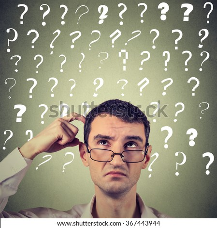 Portrait confused thinking young man in glasses bewildered scratching his head seeks a solution looking up at many question marks isolated on gray wall background. Human face expression - stock photo