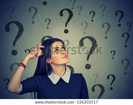 Portrait confused thinking young woman bewildered scratching head seeks a solution looking up at many question marks isolated on gray wall background. Human face expression