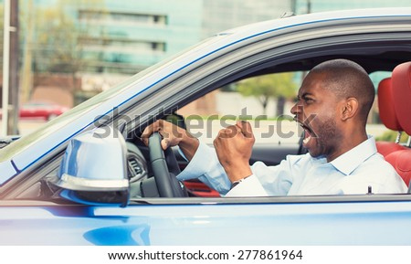 Portrait displeased angry pissed off aggressive man driving car, shouting at someone in traffic hand fist up in air side door view. Emotional intelligence concept. Negative human expression - stock photo