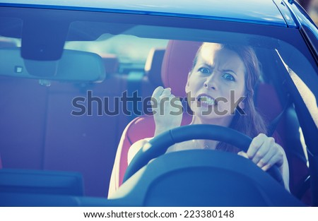 Portrait displeased angry pissed off aggressive woman driving car, shouting at someone in traffic hand fist up in air front windshield view. Emotional intelligence concept. Negative human expression - stock photo