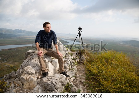 Portrait dreaming photographer sits on a mountaintop.
