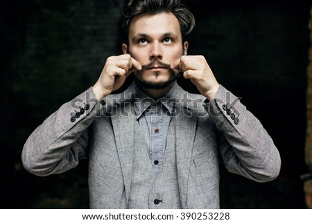 Portrait Elegant bearded vintage retro young handsome Businessman man hipster and He twists his mustache, Outdoor, jacket - stock photo