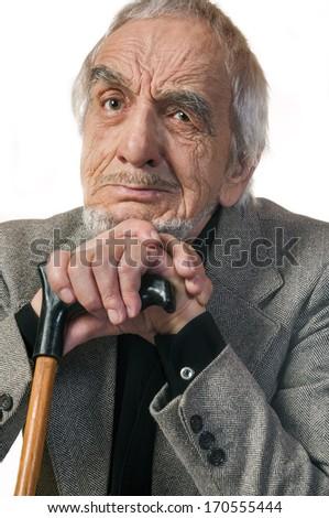 Portrait emotional elderly man leaning on a cane - stock photo