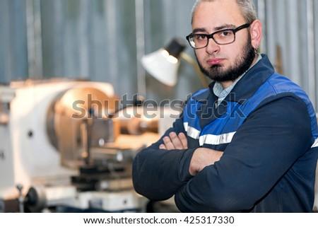 Portrait factory man turner worker on workshop lathe machine background - stock photo