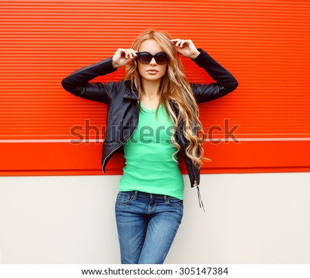 Portrait fashion beautiful woman in rock black style, wearing a sunglasses and leather jacket standing against the bright red urban wall - stock photo